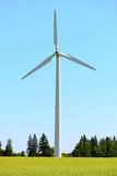 Wind generator in the meadows, on a background of blue sky. Royalty Free Stock Photo