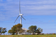 Wind generator towering above an old farm house Stock Photo