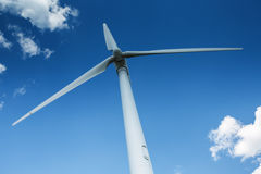 Wind generator turbine against deep blue sky with clouds stock photography