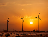 Wind generator turbines sihouettes on sunset Royalty Free Stock Image