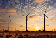 Wind generator turbines sihouettes on sunset Stock Photos