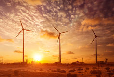Wind generator turbines sihouettes on sunset Royalty Free Stock Images