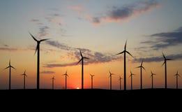 Wind generators. Wind turbine farm over sunset Stock Photo