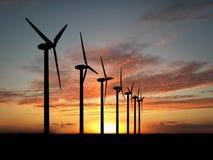 Wind generators. Wind turbine farm over sunset Royalty Free Stock Photo