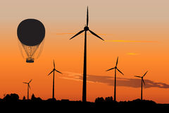 Wind generators and Air Baloon in sunrise Royalty Free Stock Images