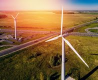 Wind generators on background of solar panels, ring road, truck and small forest areas bright summer Sunny day royalty free stock photography