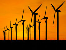 Wind generators over orange sky. Wind turbine farm over sunset (see more in my portfolio Royalty Free Stock Photography