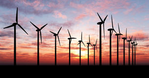 Wind generators over orange sky. Wind turbine farm over sunset Royalty Free Stock Images