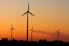 Wind generators in sunrise. Four windturbines against dramatic sunset producing environment friendly energy Stock Photography