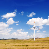Wind generators turbine and sky with clouds - ecology energy saving concept Royalty Free Stock Images