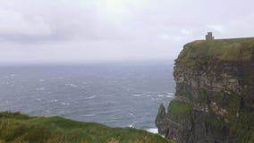 Wind, golven, overzees en gras bij de Klippen van Moher, Ierland stock footage