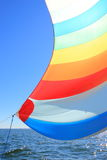 The wind has filled colorful spinnaker sail. The wind has filled the spinnaker on sailing yacht. Detail of a colorful sail against the deep blue sky Royalty Free Stock Images