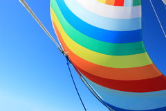 The wind has filled colorful spinnaker sail. The wind has filled the spinnaker on sailing yacht. Detail of a colorful sail against the deep blue sky Stock Photo