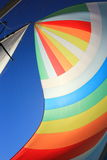 The wind has filled colorful spinnaker sail. The wind has filled the spinnaker on sailing yacht. Detail of a colorful sail against the deep blue sky Stock Photos