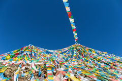 The wind-horse flags against a blue sky in tibet. The wind-horse flags on tibetan snow mountain,the symbol of harmony among heaven,earth,human beings and animals royalty free stock images