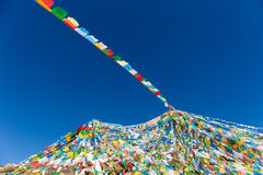 The wind-horse flags on tibet against a blue sky. The wind-horse flags on tibetan snow mountain,the symbol of harmony among heaven,earth,human beings and animals stock images