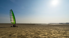 Wind and human power at Bagan Lalang beach. SELANGOR, MALAYSIA - 10TH FEBRUARY 2015; A young man uses a wind to move his tricycle in Bagan Lalang beach at Stock Images