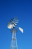 Wind mill. Retro metallic Wind mill with the blue sky as background Stock Images