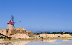 Wind Mill and covered heaps of salt. This old wind mill near Trapani in Sicilia, Italy was used to pump seawater. This was stored in ponds and let to dry. When Stock Photo