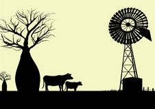 Wind mill and cows silhouette Stock Photos