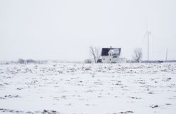Wind mill and farmhouse in snow field Stock Photography