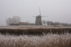Wind mill in the mist. Wind mill in mist along canal in Dutch polder royalty free stock photo