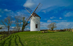 Wind mill. On a mound with blue sky and clouds stock photo