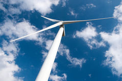 Wind mill power generator. Against blue cloudy sky Stock Images