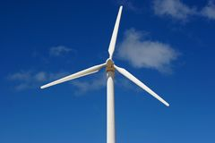 Wind mill power generator. With land against blue sky Royalty Free Stock Photos