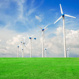 Wind mill power plant in green field  against blue sky Royalty Free Stock Images
