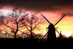Wind mill silhouette. Silhouette of a wind mill against a red sky stock photography