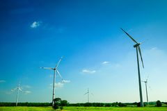 Wind mill turbines generating electricity in the green farmer`s field. Eco power. stock images