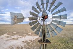 Wind mill and water pump. Close aerial view at old wind mill and water pump in prairie of northern COlorado stock photo