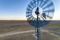 Wind mill and water pump. Close aerial view at old wind mill and water pump in prairie of northern COlorado royalty free stock image