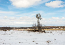 Wind mill. Winter wind mill snow on the ground clouds in the sky Stock Image