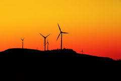 Wind mills. Silhouettes of landscape with wind mills royalty free stock photos
