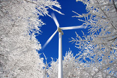 Wind mills power generators against winter forest Royalty Free Stock Photos