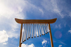 Wind musical chimes on the background of blue summer sky. Wind musical chimes on the background of blue cloudy summer sky Royalty Free Stock Photos