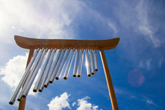 Wind musical chimes on the background of blue summer sky. Wind musical chimes on the background of blue cloudy summer sky Royalty Free Stock Photo