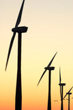 Wind park silhouettes at dawn. Several windmill silhouettes at sunrise Stock Images
