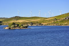 Wind Power. Wind turbines, used to generate clean electricity, next to a water dam Stock Image