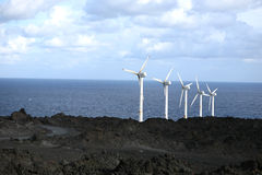 Wind power. A row of wind wheels at the coast of a volcanic island generating clean power royalty free stock image