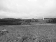 Wind power. A black and white landscape of wind turbines set with green trees and grass on a cloudy day Stock Photo