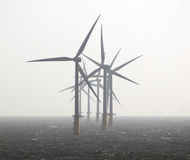 Wind power eco energy. Wind power turbines offering an eco friendly electricity energy source out at sea Stock Photo