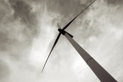 Wind power energy, windmill turbine. Monocrome modern windmill or wind turbine with dramatic skies, wind power and alternative energy resource. Producing clean stock photography