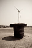 Wind power generator and bollard. Wind power generator stand with the bollard Royalty Free Stock Photo