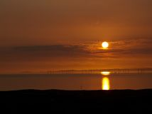 Wind power. Green energy and great view of beautiful sunset and sea Stock Images