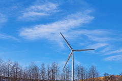 Wind power mill against blue sky and clouds. Ecologically friendly wind turbine is part of the forestry landscape Royalty Free Stock Images