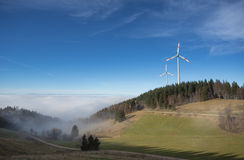Wind power mills above fog in black forest, Germany Royalty Free Stock Photos