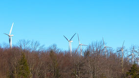 Wind power mills against blue sky. Ecologically friendly wind turbines are part of the forestry landscape Stock Photography